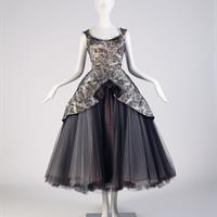 Gown by American designer Charles James (1906 – 1978, career in New York), sleeveless dress; its boned bodice and undulating peplum are of black lace over ivory silk satin. These two layers are pleated at the center-front then applied to black silk faille and interfaced with black Pellon® and stiff tulle