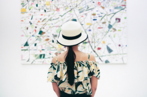 A woman in a white hat stares at an abstract painting hanging on a gallery wall