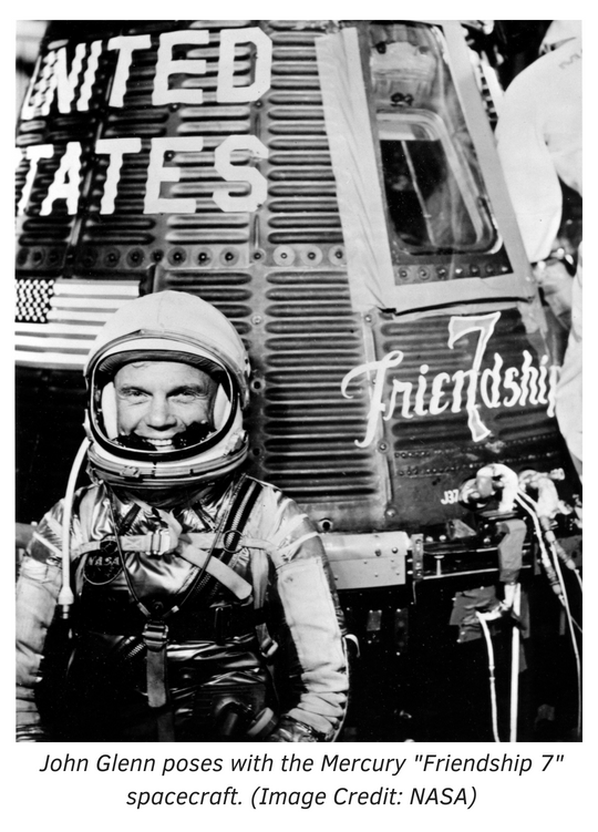 John Glenn poses with the Mercury Friendship 7 spacecraft.