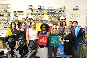 Ohio Arts Council staff members hold multicolored bags they screen printed at a workshop at Blockfort.