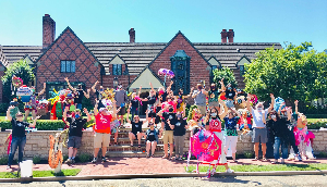 A group of people wearing colorful t-shirts and face masks stand in front of a brick building on a sunny day.
