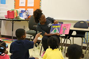 A photo of a woman sitting in the front of a classroom reading a picture book to children.