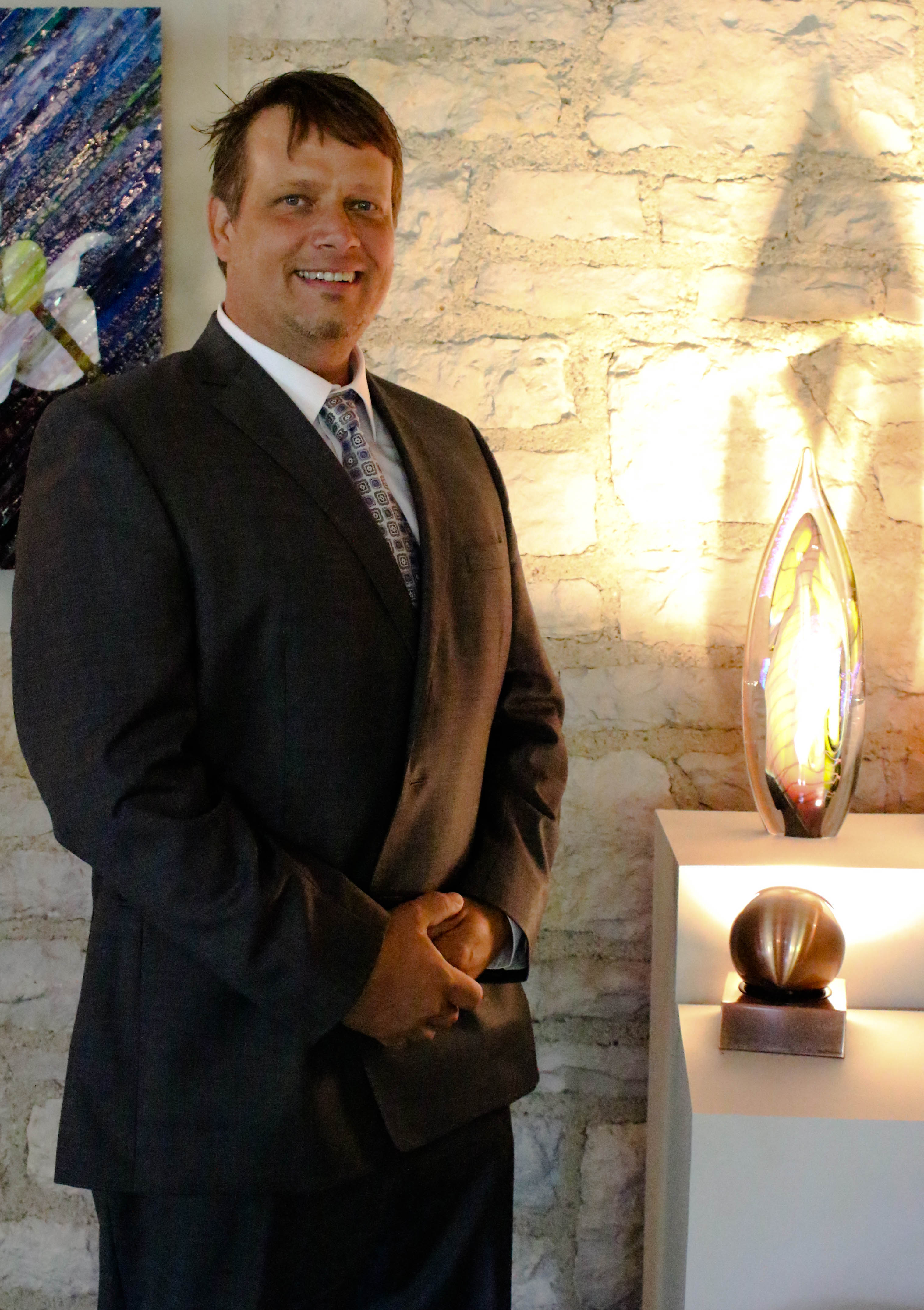 Matthew J. Paskiet, a Holland-based glass artist, stands by one of his pieces, currently on exhibit through September 2017 at the Ohio Governor's Residence in Bexley, Ohio.