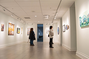 Visitors look at art on view at the 12th Annual OOVAR Juried Exhibition