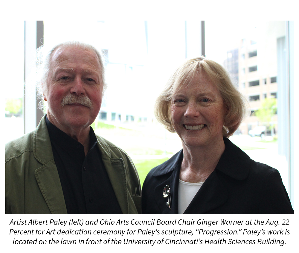 "Artist Albert Paley and Ohio Arts Council Board Chair Ginger Warner at the Aug. 16  Percent for Art dedication ceremony for Paley's sculpture, ""Progression."" Paley's work is located on the lawn in front of the University of Cincinnati's Health Sciences Building."