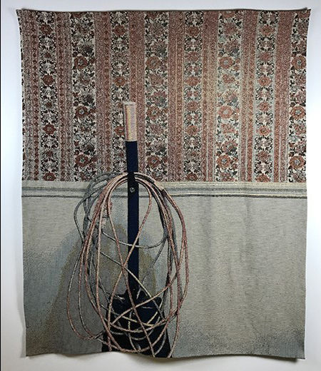 Image of vacuum with many cords in front of a wall covered in wallpaper.